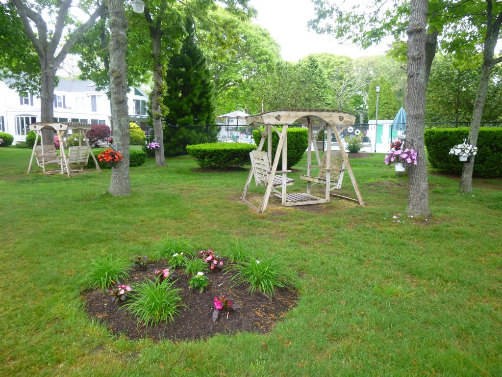 Hanging impatiens and small flower garden near wooden swings